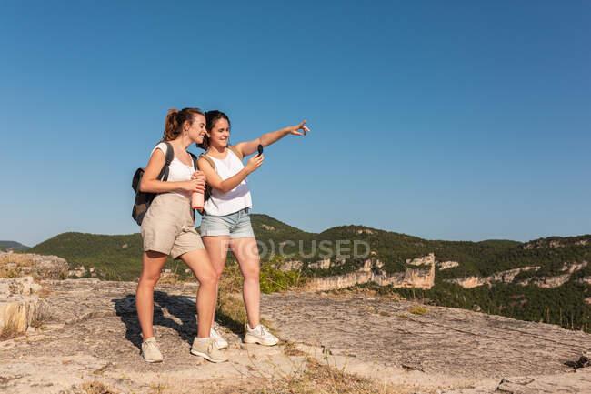 Jóvenes viajeros jóvenes felices en ropa de verano usando brújula juntos mientras están de pie en un exuberante terreno montañoso soleado - foto de stock