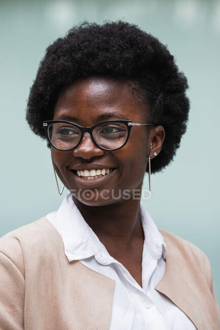 Portrait of delighted African American female entrepreneur with Afro hair and in smart casual outfit standing against glass building looking away — Stock Photo