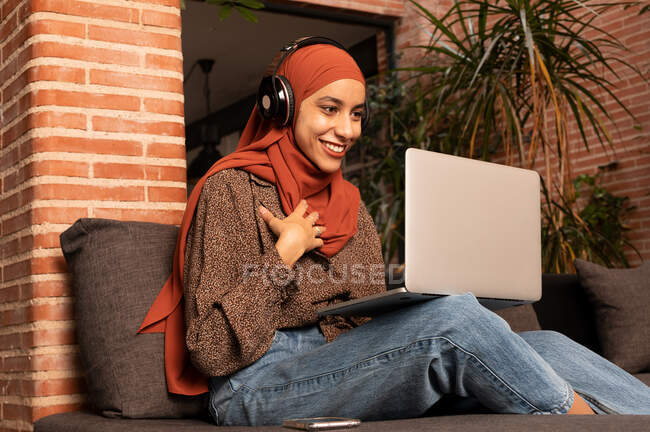 Cheerful Muslim female in wireless headphones and headscarf having video call via netbook and sitting on comfy sofa — Stock Photo