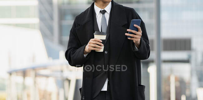 Cropped unrecognizable young well dressed ethnic male executive with cellphone and hot drink to go in city — Stock Photo