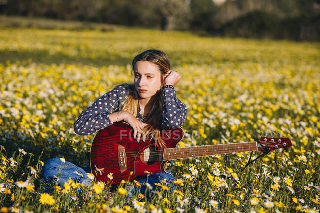 Thoughtful young hipster woman sitting on a meadow in the countryside writing songs on notebook and playing guitar during summer sunlight — Stock Photo