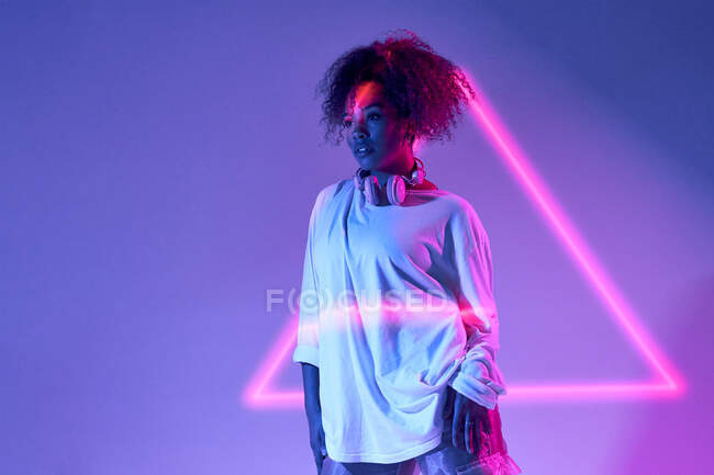 Confident young African American female with curly hair standing looking away in neon lights — Stock Photo