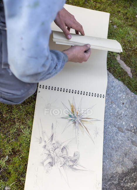 From above of crop anonymous male artist turning page of album with sketches in nature — Stock Photo