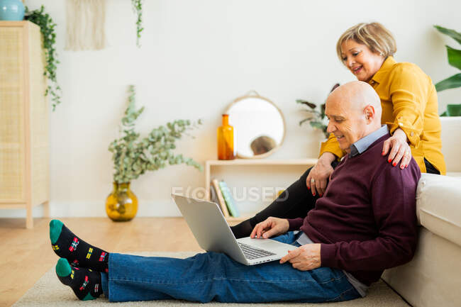 Cheerful mature couple talking on video chat on laptop in living room — стокове фото