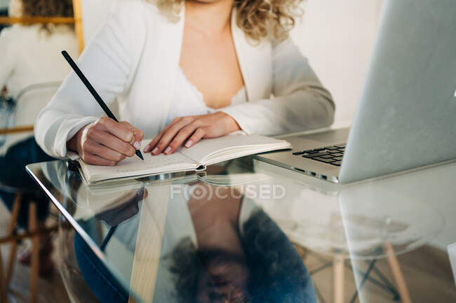 Crop anonymous female student with curly hair in casual clothes sitting at glass table and taking notes in copybook while preparing for exams using laptop at home — Stock Photo