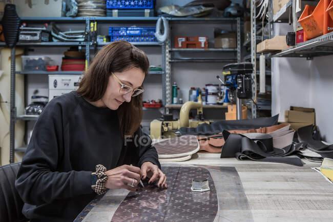 Vista lateral do artesão conteúdo criativo feminino sentado na bancada e marcando pedaço de couro para estofos assento da motocicleta — Fotografia de Stock