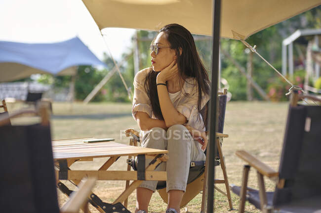 Beautiful ethnic Asian female in sunglasses sitting at table while having a relaxing time in camping area during holidays looking away — Stock Photo