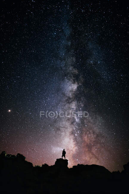 Low angle of silhouette of anonymous tourist standing with light torch on head on cliff against glowing starry sky at night — Stock Photo