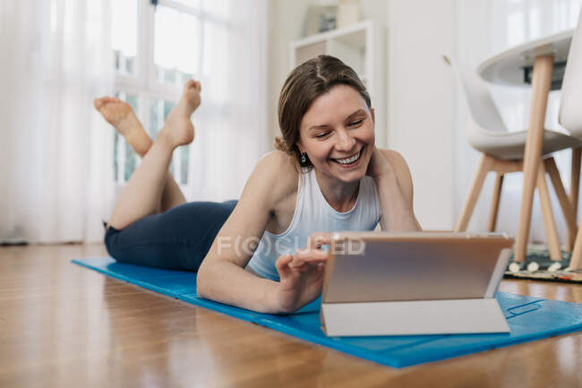 Encantada fêmea magra deitada no tapete e no tablet de navegação enquanto escolhe a lição on-line para praticar ioga — Fotografia de Stock