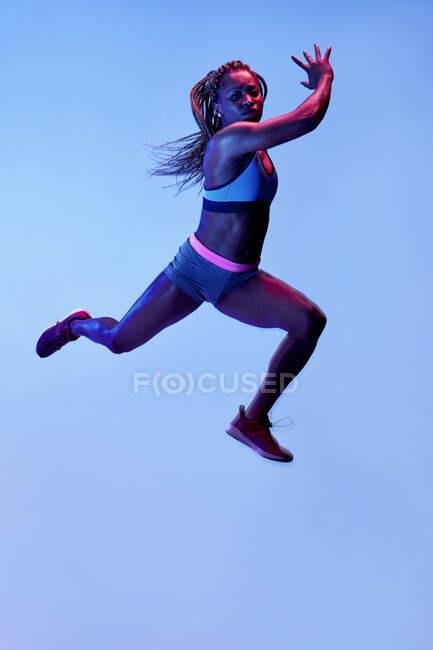Вид сбоку решительной афроамериканки, прыгающей с летящими волосами, глядя вперед во время кардиотренировки — стоковое фото