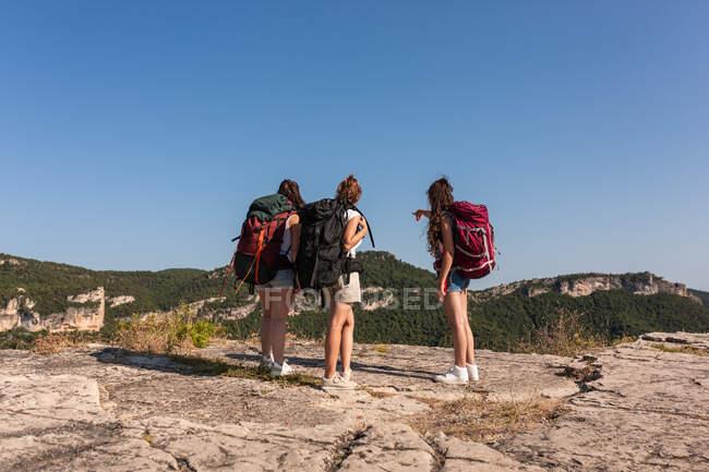 Погляд на групу невпізнаних жінок - рюкзаків, що стоять на пагорбі у високогір