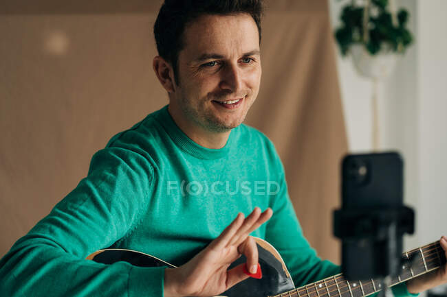 Crop cheerful adult male vlogger with guitar and plectrum recording video tutorial on cellphone at home — Stock Photo