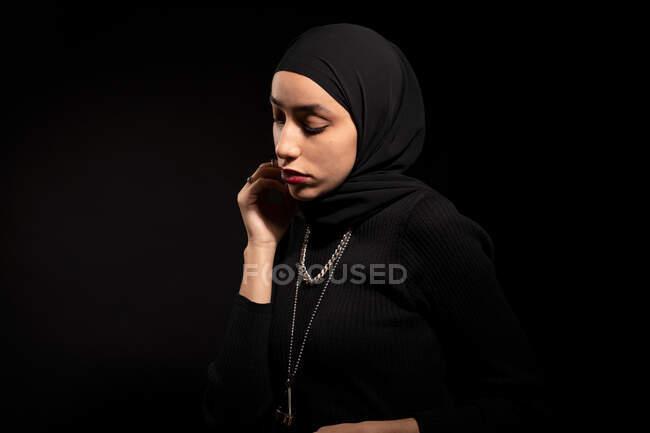 Attraente giovane donna islamica vestita di nero e hijab che distoglie delicatamente lo sguardo sullo studio nero — Foto stock