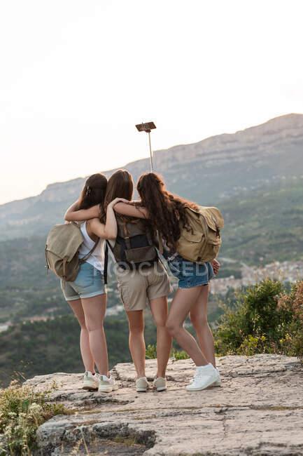 Ззаду подорожньої самиці друзів з рюкзаками, що стоять на пагорбі і роблять собі постріл на смартфоні на тлі гірського пасма влітку. — стокове фото