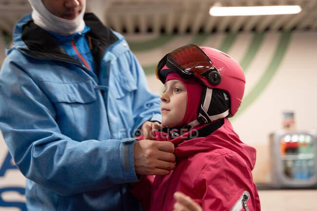 Positivo jovem pai em activewear quente e balaclava esqui colocando capacete protetor na cabeça filha bonito no centro de esqui moderno — Fotografia de Stock
