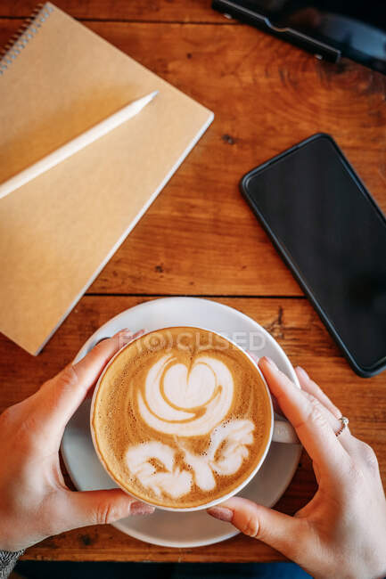 Top view of anonymous woman about to have coffee with a drawing of a flower in the coffee foam next to a smart phone — Stock Photo
