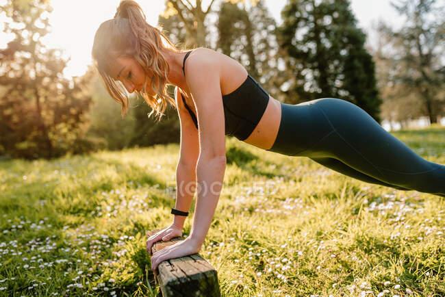 Вид сбоку молодой спортсменки в спортивной одежде, работающей на газоне с деревянным блоком сзади освещенным — стоковое фото
