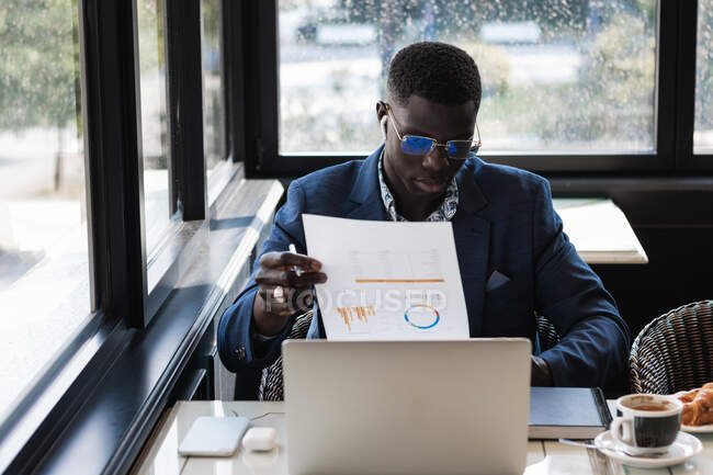 Young ethnic male entrepreneur in eyeglasses with graphic on paper working at cafe table — Stock Photo