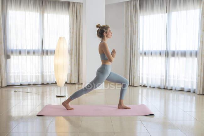 Вид сбоку на тихую стройную женщину, стоящую в Анахайасане с руками Намасте и практикующую йогу дома — стоковое фото