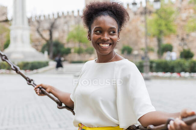 Щаслива молода афроамериканка в білій блузці, що спирається на ланцюговий бар'єр і дивиться на себе з зубатою посмішкою, проводячи теплий день на міській площі. — стокове фото