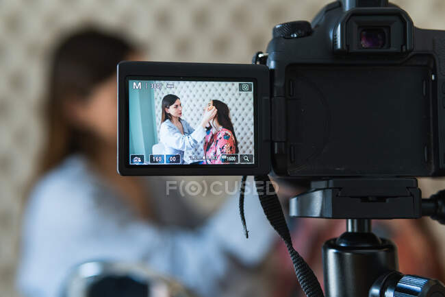 Smiling professional female makeup artist applying foundation on content model face and recording video tutorial for vlog — Stock Photo