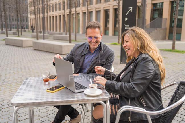 Entzücktes reifes Paar sitzt am Tisch im Café im Freien und schaut lustige Videos auf Netbook in der Stadt — Stockfoto