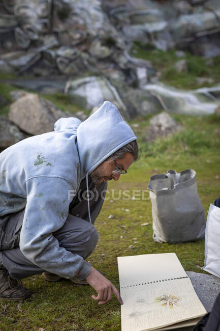 Side view male artist turning page of album with sketches in nature — Stock Photo