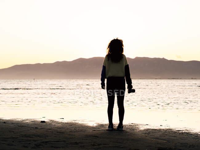 Силуэт женщины-путешественницы с фотокамерой, стоящей на берегу моря на закате — стоковое фото