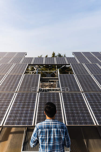 Back view anonymous professional technician wearing checkered shirt checking photovoltaic panels in solar power station on clear sunny weather — Stock Photo