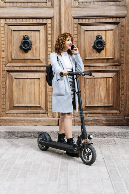 Full body smiling young African American female in warm clothes talking on mobile phone while standing on sidewalk with scooter and looking away — Stock Photo