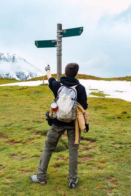 Visão traseira do mochileiro fêmea apontando na seta mostrando a direção do caminho de pé contra o pólo no Pico da Europa — Fotografia de Stock