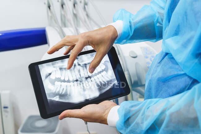 Cortado ortodoncista irreconocible en uniforme estéril demostrando imagen radiográfica en la pantalla de la tableta durante el chequeo en el hospital - foto de stock