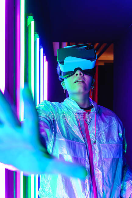 Anonymous female in modern headset with outstretched arms exploring virtual reality in purple light — Stock Photo