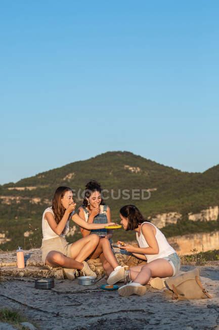 Compagnia di giovani amiche in viaggio sedute in collina e che mangiano al tramonto negli altopiani — Foto stock