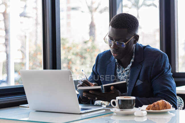 Concentrated African American male entrepreneur writing in notepad while sitting at table with laptop and working in cafe — Stock Photo