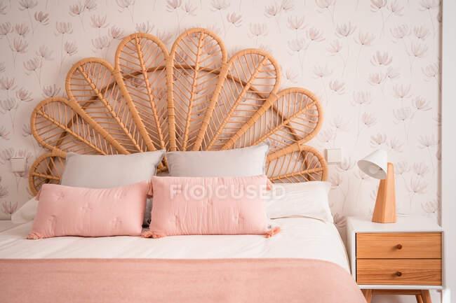 Comodo letto di testiera in rattan vintage naturale carino con cuscini ornamentali in una stanza — Foto stock