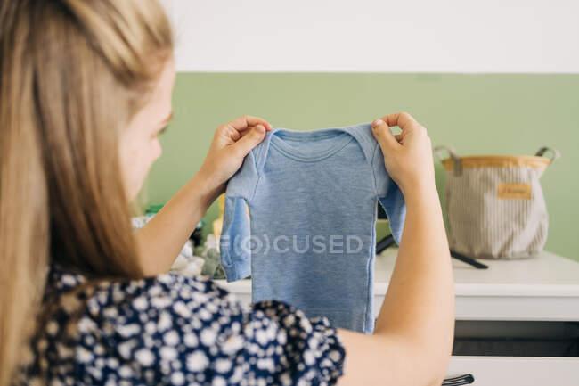 Вид сзади на молодую женщину с прямыми каштановыми волосами, открывающими ящик и вынимающими детскую одежду дома — стоковое фото