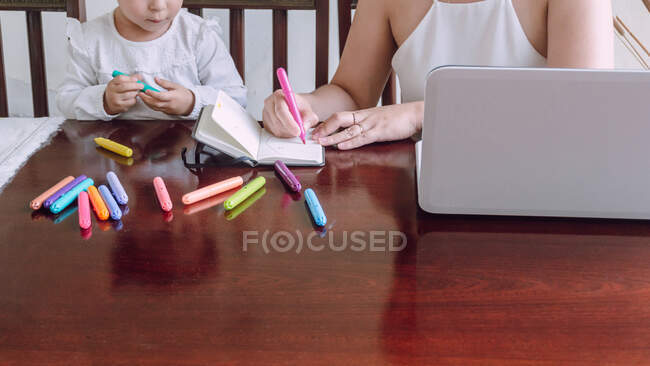 Crop unrecognizable woman and little child sitting at table and drawing with markers in notebook — Stock Photo