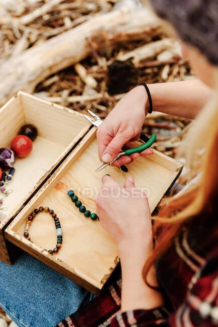 De cima cultura artesão anônima criando bijouterie artesanal ao usar pedras semipreciosas e sentado na praia perto do mar — Fotografia de Stock