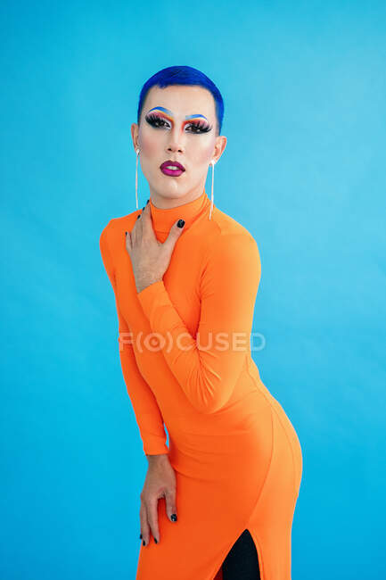 Calma delgada drag queen con el pelo teñido de azul con vestido naranja tocando el cuello y mirando a la cámara mientras está de pie sobre fondo azul - foto de stock