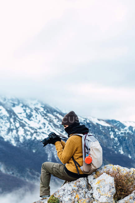 Side view female tourist with backpack using photo camera while shooting amazing nature of Peaks of Europe during trip — Stock Photo