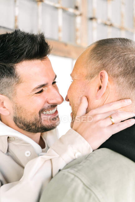 Side view of happy young multiracial gay couple hugging and looking at each other on street on sunny day — Stock Photo
