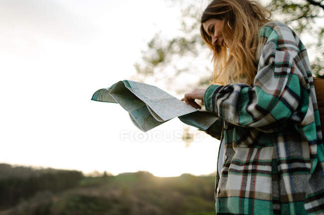 From below smiling female watching paper guide on lawn under light sky during summer trip — Foto stock