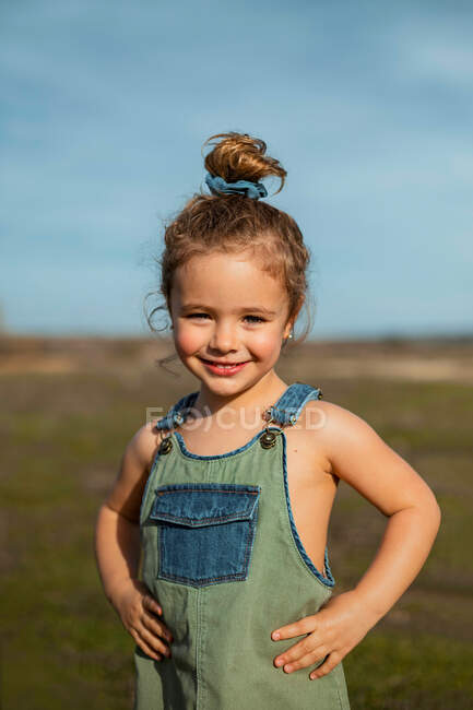 Очаровательная маленькая девочка в комбинезоне, стоящая с руками на талии на лугу и смотрящая в камеру — стоковое фото
