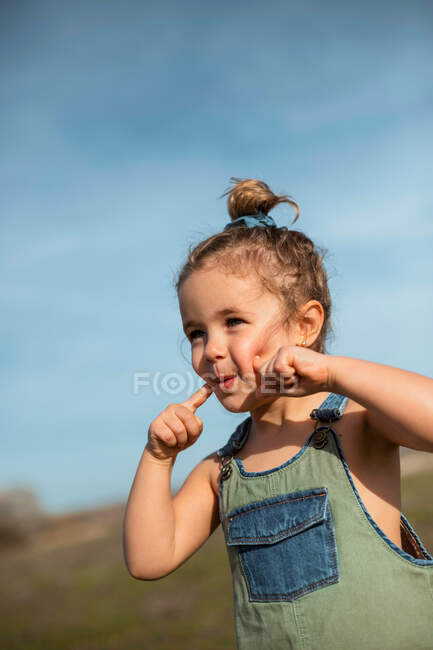 Encantada niña adorable en overoles de pie con los dedos en la cara en el prado y mirando hacia otro lado - foto de stock