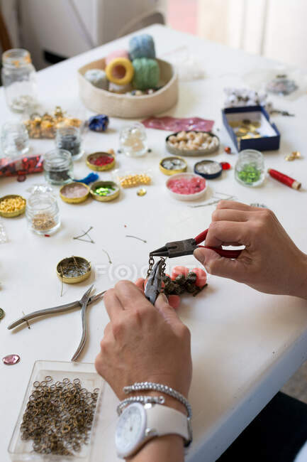 High angle of crop anonymous female designer with pincers sitting at table with various beads — Stock Photo
