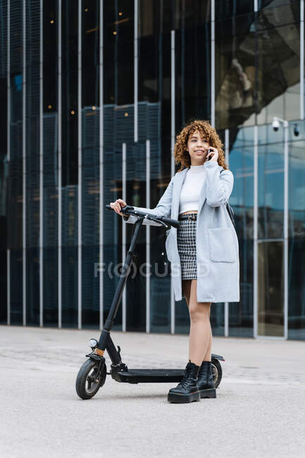 Full body of positive young African American female in blue coat having conversation via smartphone while standing on sidewalk with scooter — Fotografia de Stock