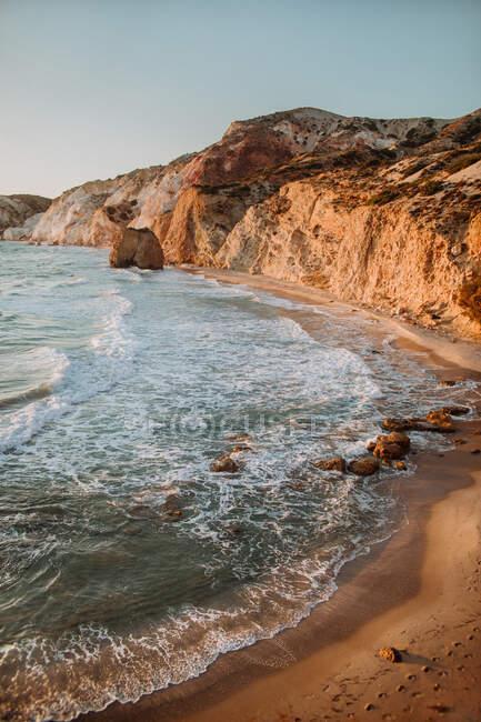 Paesaggio pittoresco di ruvida riva del mare pietroso lavato agitando il mare caldo sotto il cielo blu senza nuvole in Fyriplaka Milos sul tempo soleggiato — Foto stock