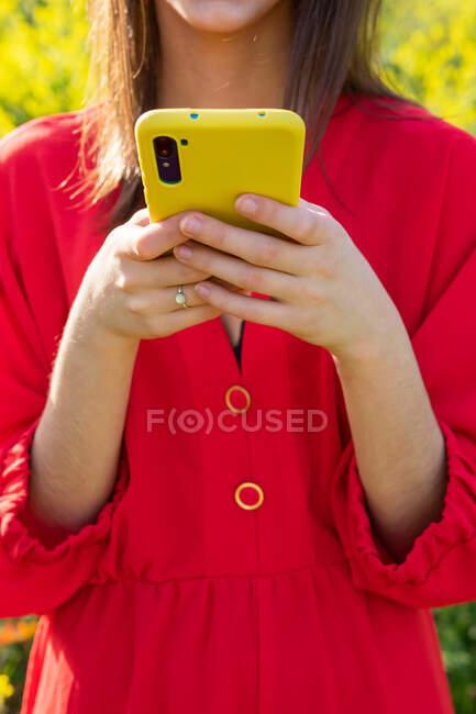 Mulher de colheita em vestuário vermelho mensagens de texto no celular contra plantas florescentes na luz solar — Fotografia de Stock