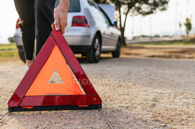 Crop anonymous male driver placing red emergency triangle on country road near broken car - foto de stock